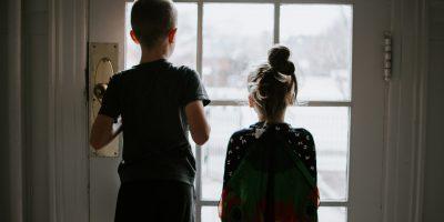 Zwei Kinder vor einem Fenster