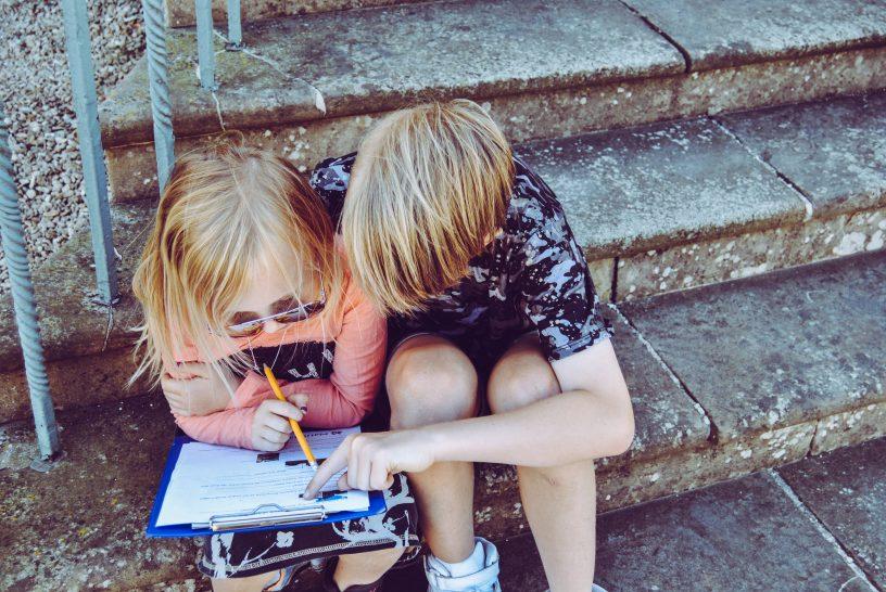 Mädchen und Junge sitzen mit einem Buch auf der Treppe
