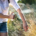 Frau sprüht Insektenschutz auf